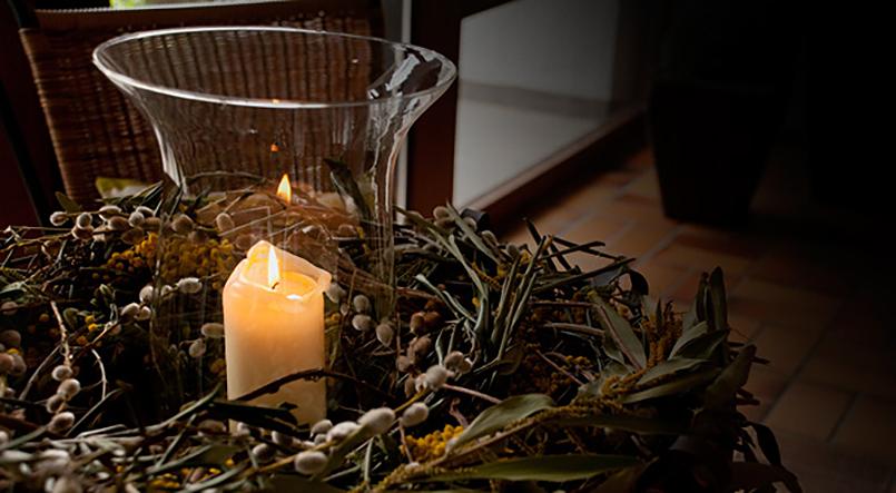 Kerze in einem Windlicht in einem Kranz aus verschiedenen Zweigen