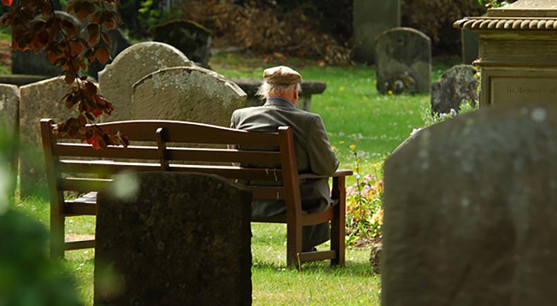 Älterer Herr von hinten sitzt auf einer Bank auf dem Friedhof