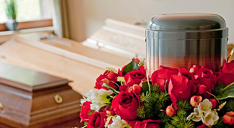Särge und eine Urne mit Blumenschmuck